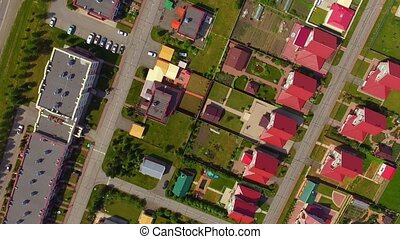 Aerial view shooting drone flying over the red roofs of cottages.