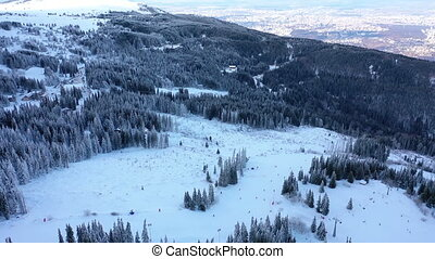 Aerial view skiers and snowboarders on ski lift on snow mountain in ski resort.