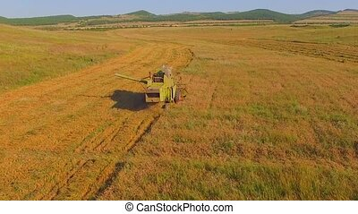AERIAL VIEW. Small farms.Old combine harvesting.