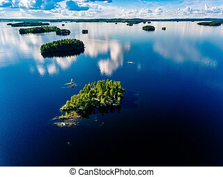 Aerial view small island in blue lake landscape with green forests on a sunny summer day in Finland.