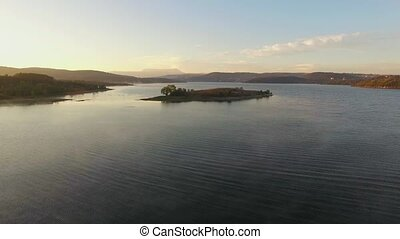 AERIAL VIEW. Small Island In The Middle Of Water Reservoir At Sunset