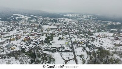 Aerial view. Snowy village in the valley of the mountains