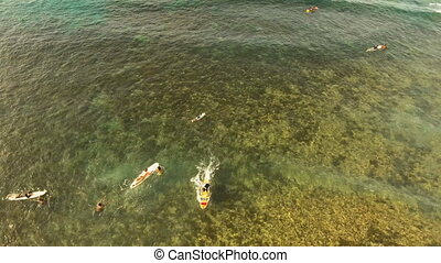 Aerial view surfers on the waves.Siargao, Philippines.