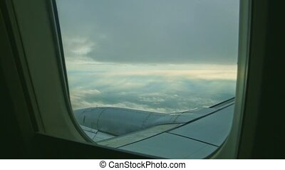aerial view through aircraft window on big steel jet engine fly above white clouds