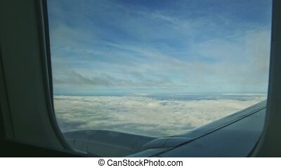 aerial view through airplane window on fluffy clouds quickly fly above jet engine