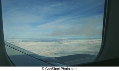 aerial view through airplane window on fluffy white clouds quickly fly by jet engine