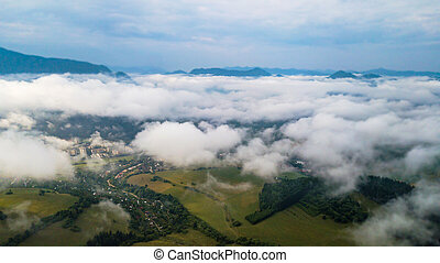 Aerial view through clouds to the city of Dolny Kubin