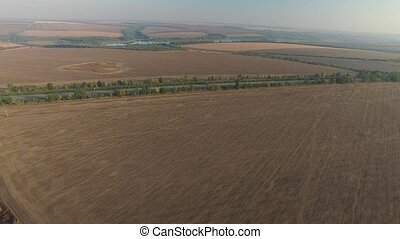 Aerial view tilled field near the highway with cars