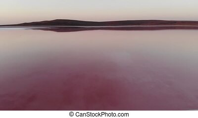 Aerial view Tilted downward shot Pink Salt Lake low key. Cinematic film grain. Evening shot.