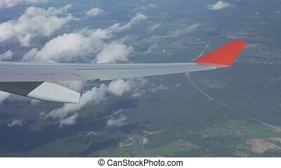 Aerial view to the wing of an airplane and cumulus clouds...