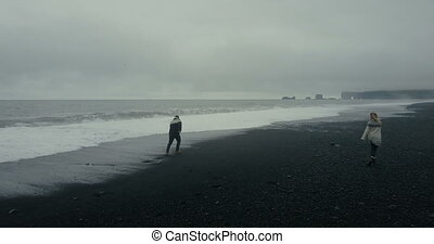Aerial view to the young couple on the black volcanic beach in Iceland. Man runs from the wave on the shore, woman waits