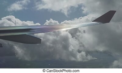 Aerial view to wing of an airplane and rays of the sun in cumulus clouds