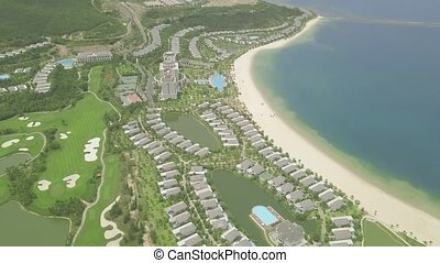 Aerial view tourist resort villas and hotels on tropical island and blue sea landscape. Drone view from above luxury cottage village with houses, swimming pool and golf course on blue sea shore.