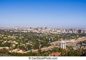 Aerial view towards the skyline of Century City commercial district; downtown area skyscrapers visible in the background; highway 405 and residential area in the foreground; Los Angeles, California