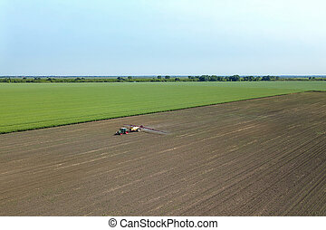 Aerial view Tractor spraying chemicals on the large field.