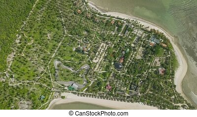 Aerial view tropical island with resort hotel on sea shore. Beautiful landscape from flying drone green island with palm tree on ocean coast.