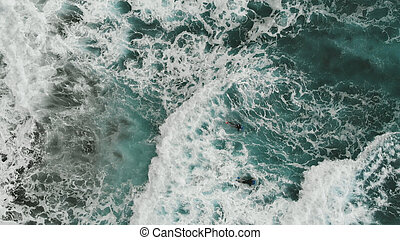 Aerial view. Two bodiserfer trying to swim through the giant waves. Cinematic view from top to down. Extreme sport. Tenerife, Canary Islands, Spain