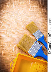 aerial view two paintbrushes with blue handles and yellow paint