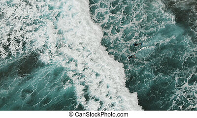 Aerial view. Two surfers trying to swim on the spot through the giant turquoise-colored waves. Beautiful view from the top down to the Atlantic coast, near the beach. Tenerife, Canary Islands, Spain