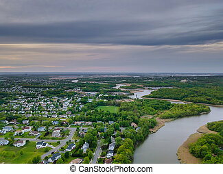 Aerial view waterfront suburban street of middle class suburban neighborhood with houses