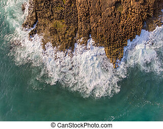 Aerial view, waves crash on a rocky shore. Portugal.