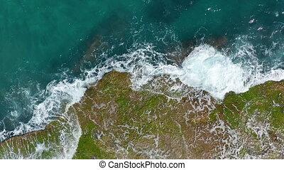 Aerial view. Waves crashing on rocks.