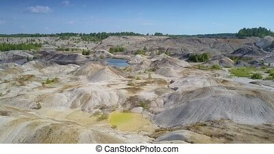 aerial view white clear hills near lake in spent clay quarry...