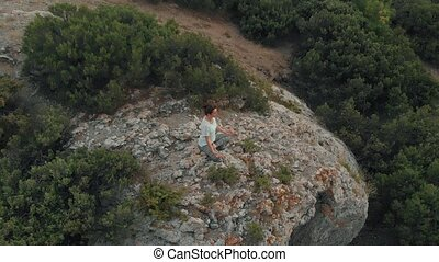 Aerial view woman meditating at sunset