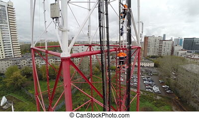 Aerial view. workers climb the TV tower - workers climb the...
