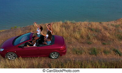 Aerial view. Young girls driving convertible car at sunset by the sea front beach. Summer adventure.