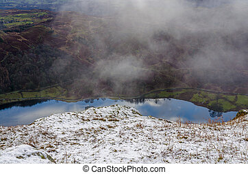 Aerial viw of reflections in Rydal Water seen from a snowy ...