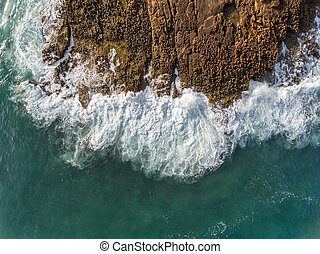 Aerial. Waves break on the rocks from the sky. Portugal