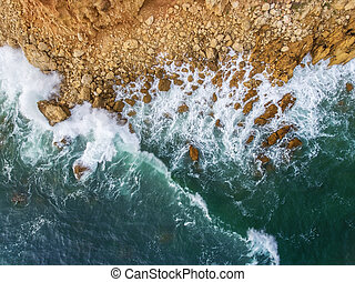 Aerial. Waves swim to the rocky shore.