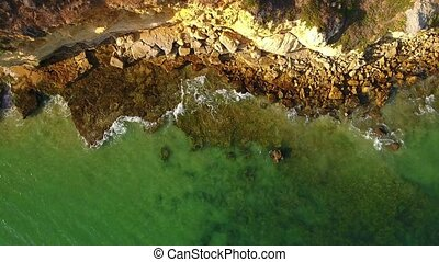 Aerial. Waves wash stones on the shore of Albufeira. Olhos...