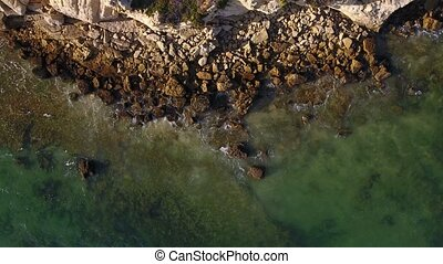 Aerial. Waves wash the stones on shore of Albufeira. Olhos de Agua