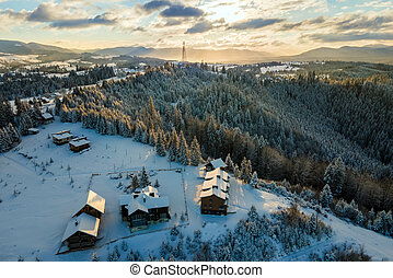 Aerial winter landscape with small village houses between snow covered forest in cold mountains in the evening.