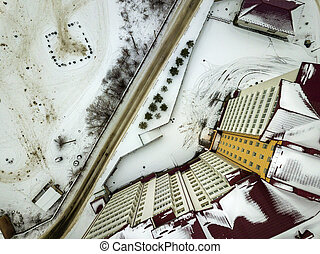 Aerial winter top view of modern big apartment building in suburb area at narrow dirty road and snowy field.