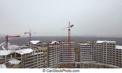 Aerial winter view of apartment complex under construction,...