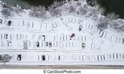 Aerila view of snow-covered cars stand in the parking lot on a winter day