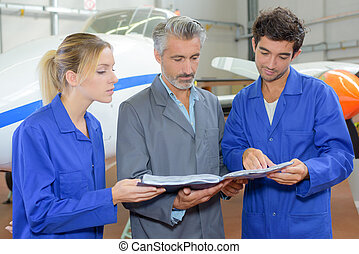 aero mechanic students and teacher revising task