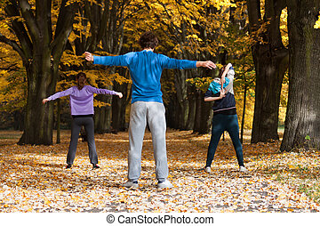 Aerobic class in the park covered with fallen leaves