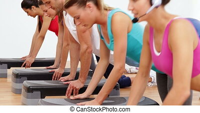 Aerobics class doing press ups together led by instructor at...