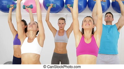 Aerobics class lifting dumbbells together at the gym