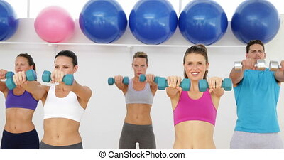 Aerobics class lifting dumbbells to