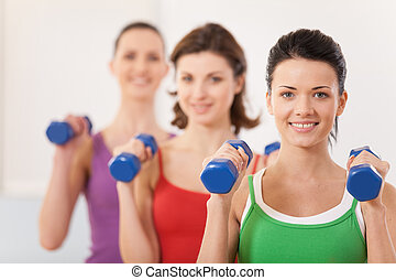Aerobics class of diverse women of different ages. girls working out in gym with dumbbells flexing their arm muscles
