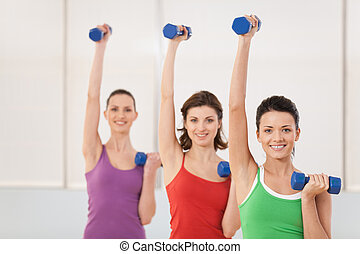 Aerobics class of women ligting weights. girls working out in gym with dumbbells flexing their arm muscles