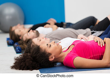 Aerobics class practising deep breathing for relaxation ...