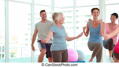 Aerobics class stepping and laughing