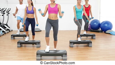 Aerobics class stepping together led by instructor and...