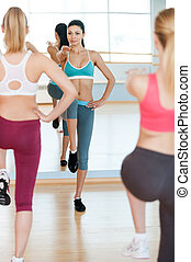 Aerobics class. Three beautiful young women in sports clothing exercising together and smiling